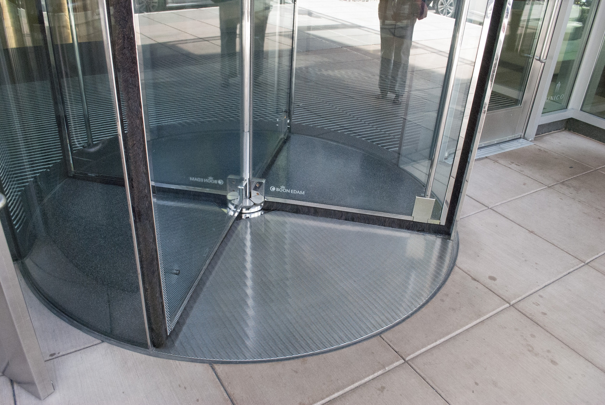 Use a matwell ring or floor frame to install an all-glass revolving door